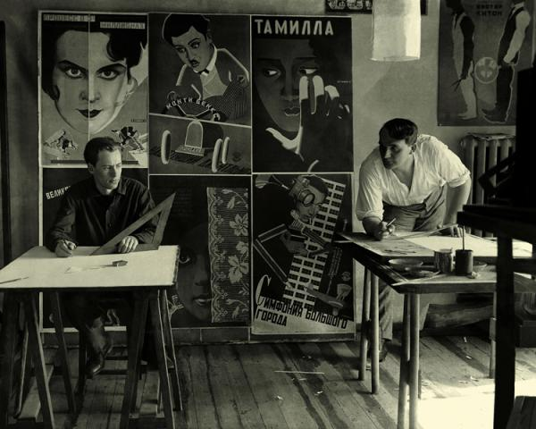 Vladimir and Gregorii Stenberg in front of some of their posters, 1928.jpg
