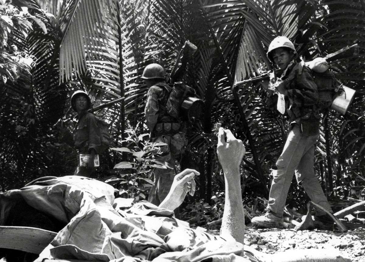 Смертельно раненый партизан Северного Вьетнама на фоне проходящих мимо южновьетнамских морских пехотинцев, осуществляющих поиск сил повстанцев в дельте Меконга
