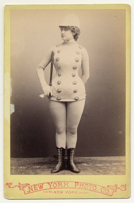 1890. Mlle Conalba in police uniform style costume with hat and baton in right hand, half-calf laced boots.