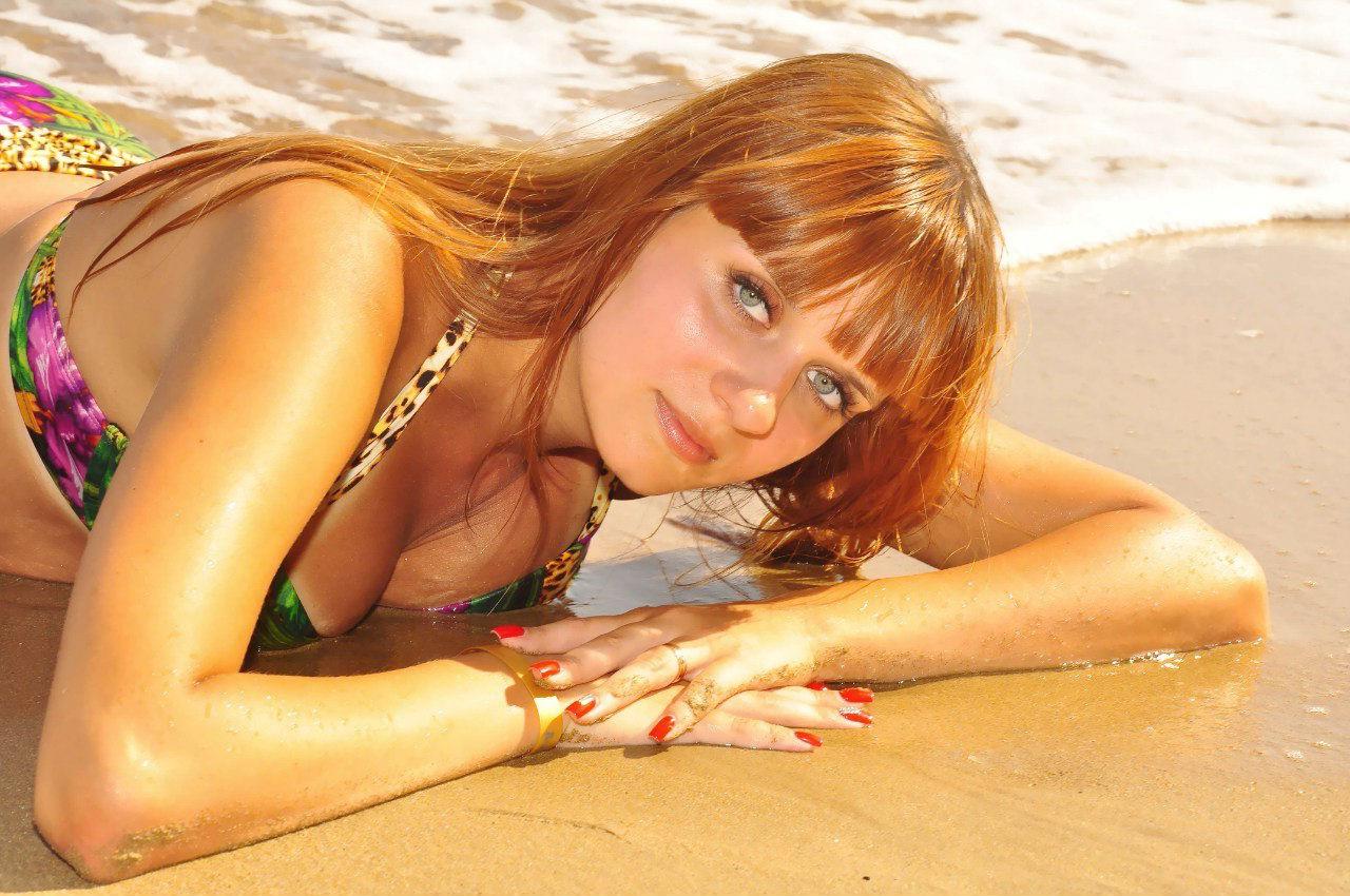 Рыжеволося девушка в купальнике на пляже