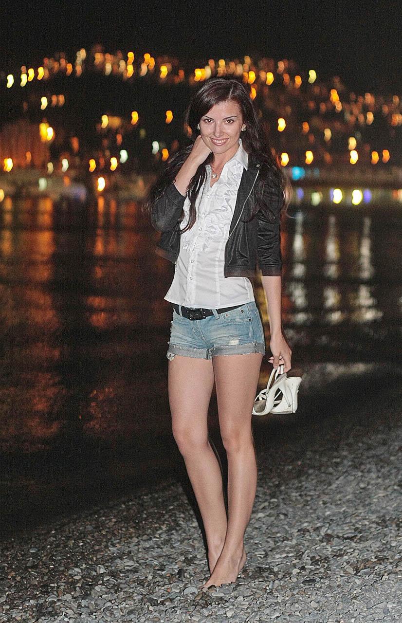 Стройная девушка на пляже в блузке и шортах