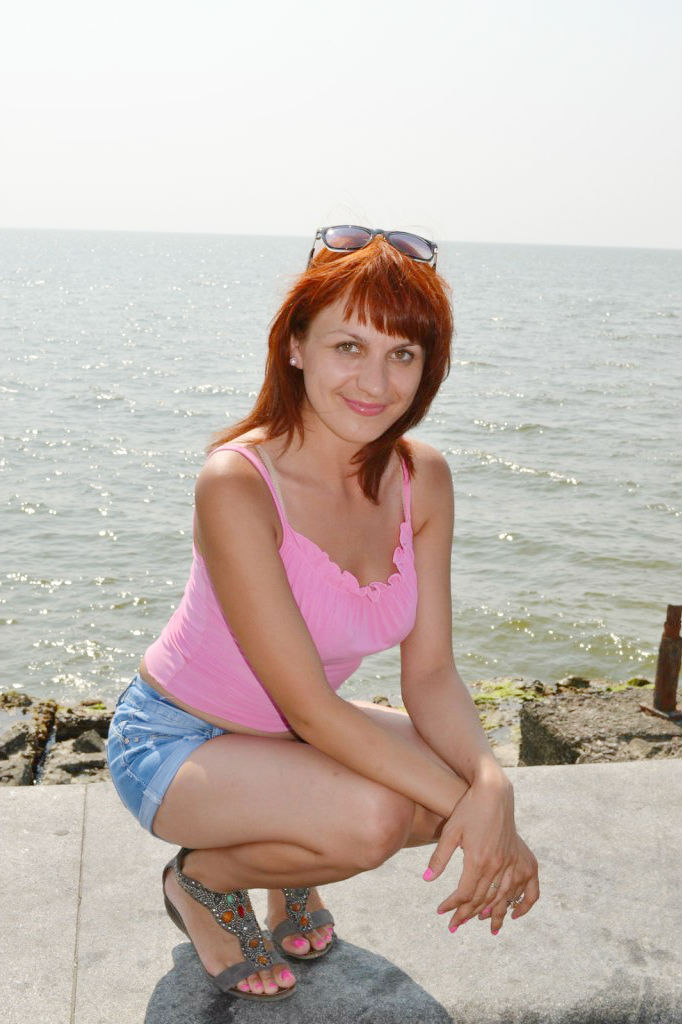 Рыжая девчонка в розовой майке на пляже