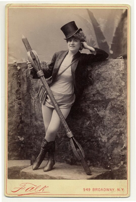 1890. Vernona Jabeau, in high boots, hat, holding a candle in a long holder.