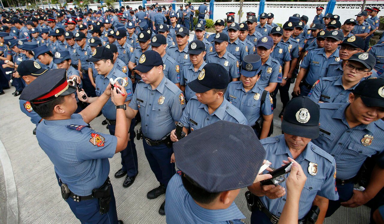 Police officers seal the muzzles of firearms during a sealing of firearms ceremony at the National Capital Region Police Office in Taguig