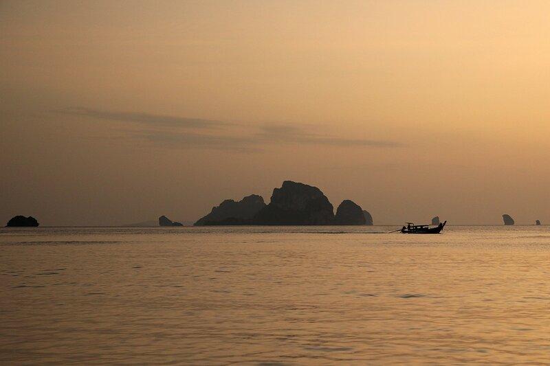 Закат на пляже Ао Нанг: острова в дымке и рыбацкая лодка