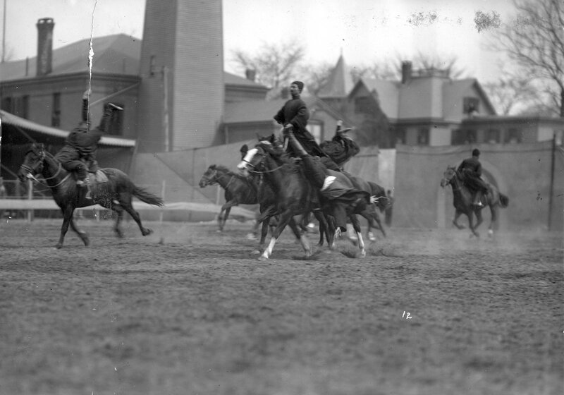 A group of Russian Georgian Cossacks led by Luka Chkhartishvili perform tricks while riding horses in a dirt arena for Buffalo Bill's Wild West Show.1901