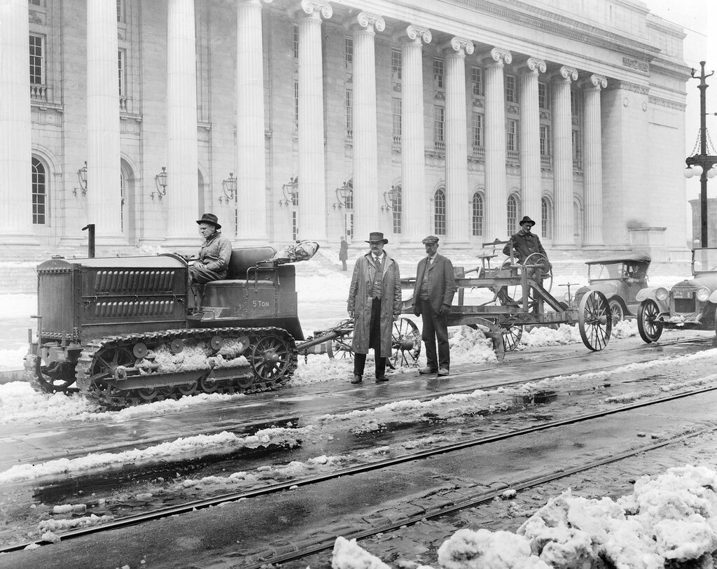 Caterpillar tractor and a snow plow cleaning snow from streets near Post Office, Stout Street in Denver, Colorado, between 1910 and 1919