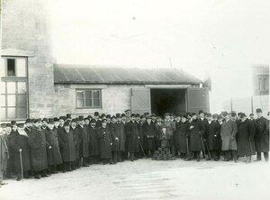 Группа акционеров и сотрудников завода у входа в заводское помещение.