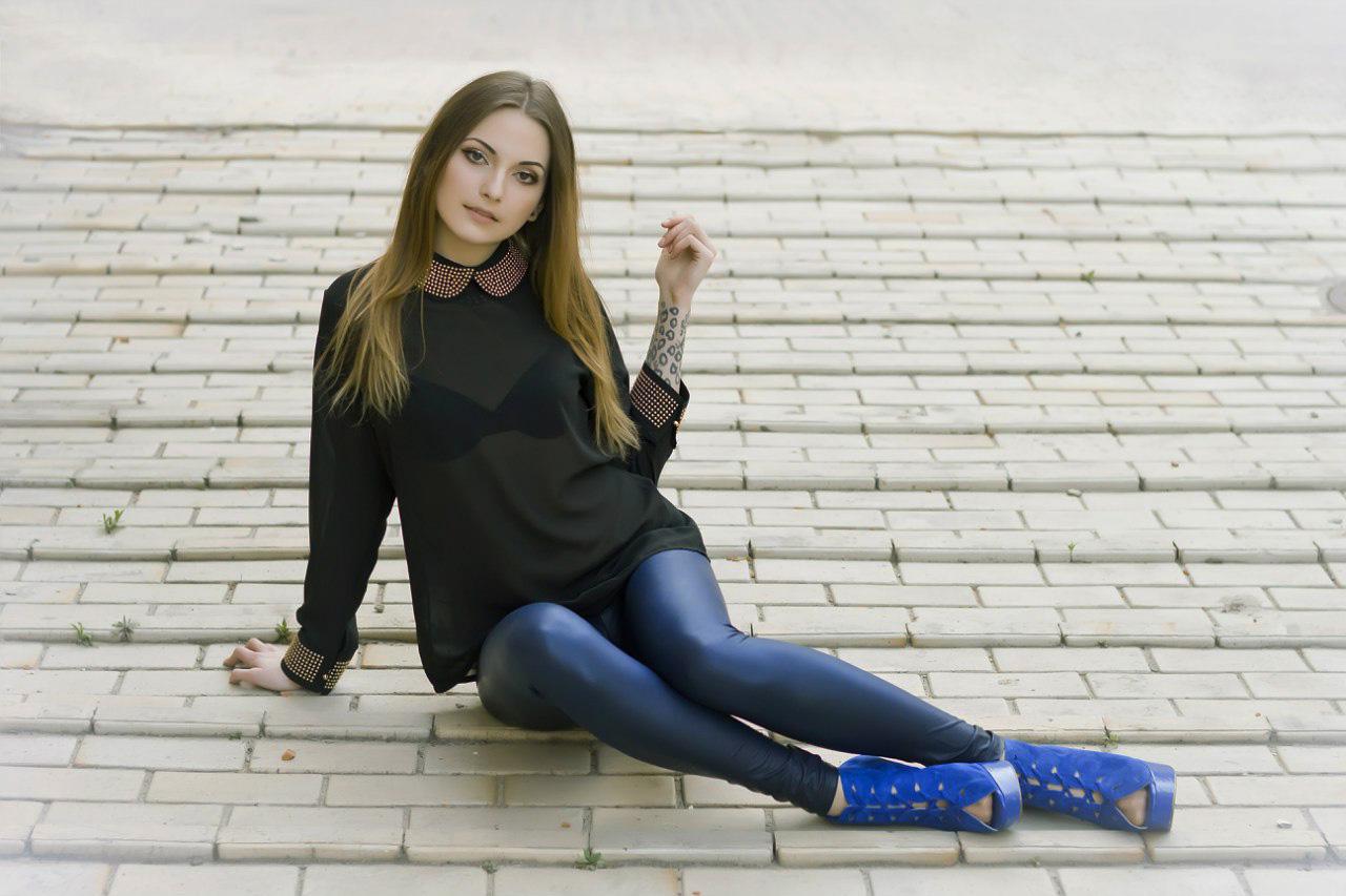Фото девушки в синих леггинсах на скамейке