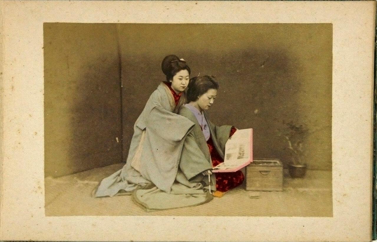 Две девушки разглядывают фотографии в альбоме