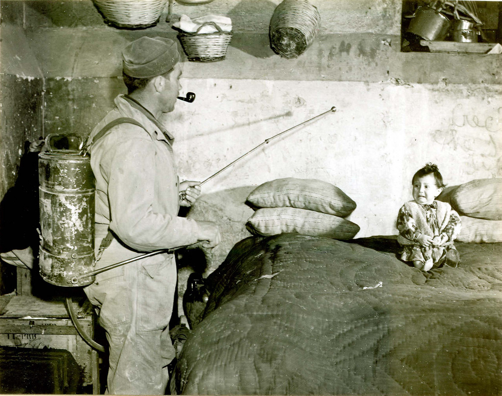 A GI spraying a DDT-kerosene mixture on top of a bed and child, while smoking a pipe, in a southern Italy house, during post-WWII Mediterranean antimalarial campaign. 1945.jpg