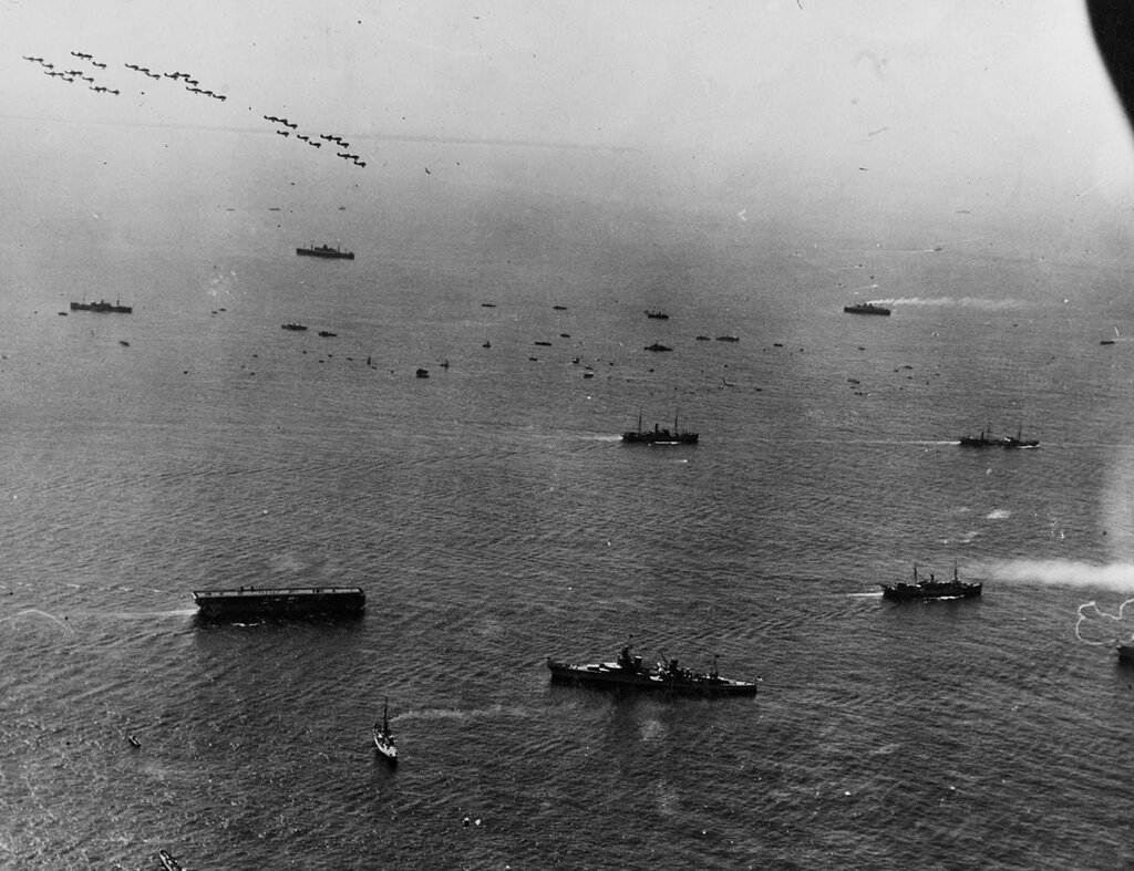 Fleet arriving off Ambrose lightship for fleet review, New York, 31 May 1934. Formations of Navy planes are overhead. USS LANGLEY (CV-1) at right