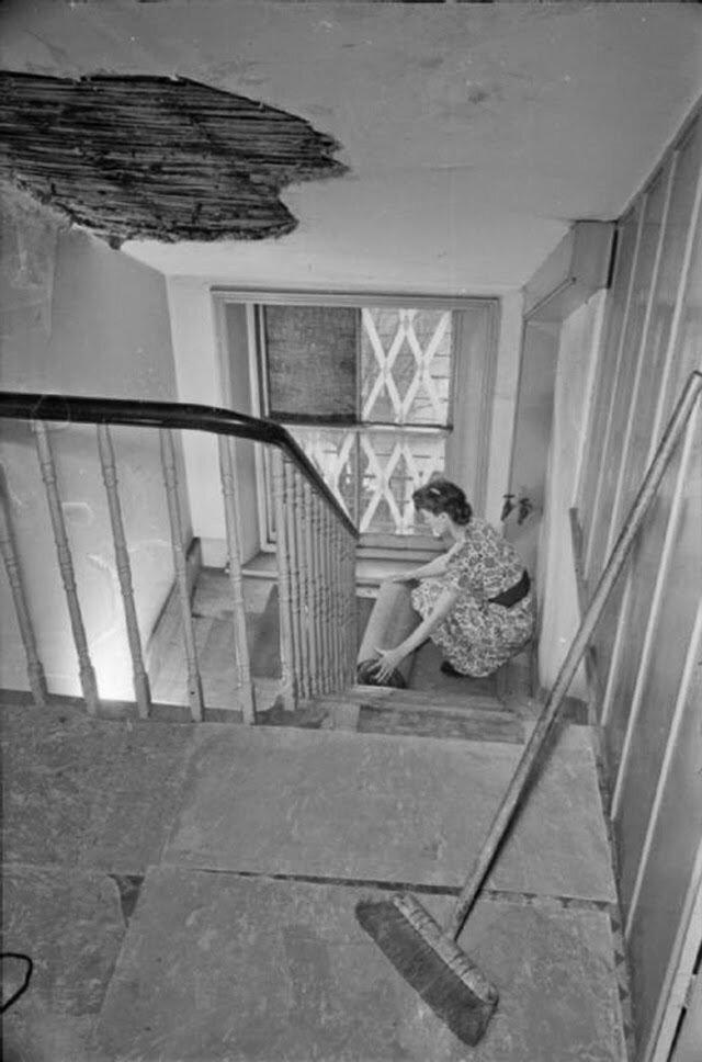 08. Оливия скатывает ковер с лестницы своего дома. Все ковры убраны и на их место положены асбест, в целях предупреждения последствий попадания зажигательных бомб