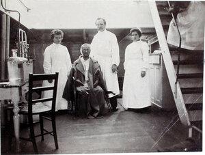 Младший врач В. П. Ивакин и сестры милосердия около больного в палате № 3.