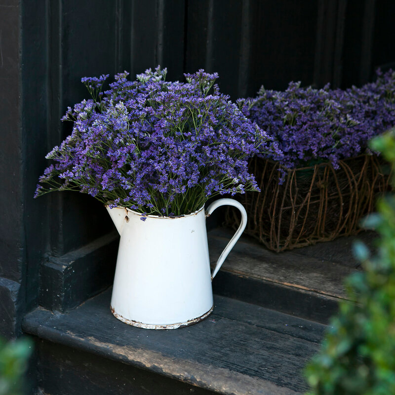 lavender in a beautiful vase costs on an old steps near the black wooden wall