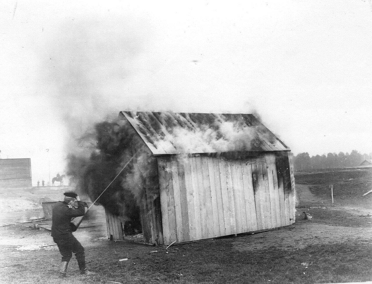 13. Пожарный тушит огнетушителем горящее здание во время испытания огнетушителей новых систем