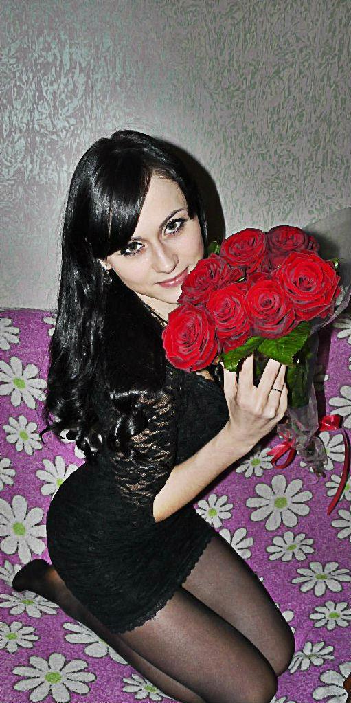 Брюнетка в колготках с букетом роз