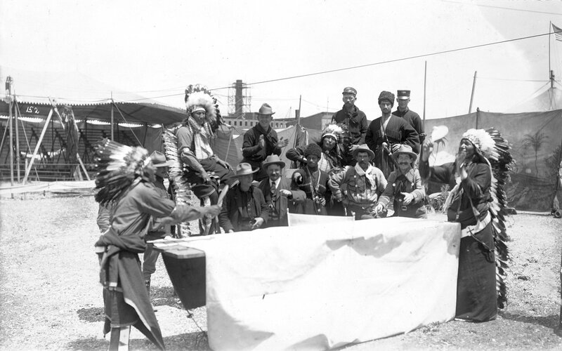 Two Native American men play ping pong while, the spectators include Native American men, cavalrymen and a few Russian Cossacks in uniform,1901