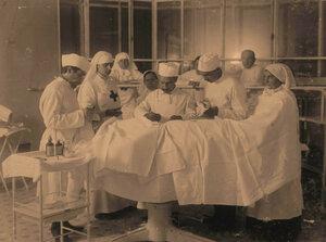 Группа врачей и сестер офицерского лазарета во время операции;2-я слева стоит-старшая сестра лазарета Л.В. Никитина.