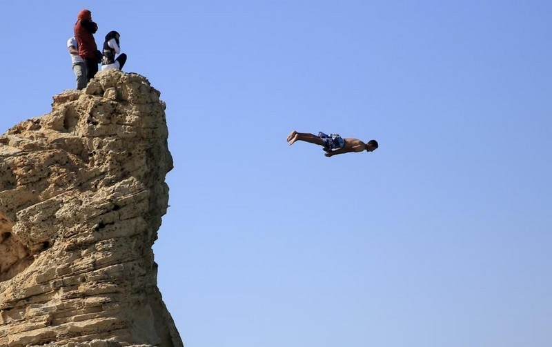 Visitors react on the rock as a man jumps into the water, above Cleopatra's Beach, on a summer's day before the start of the holy month of Ramadan, which begins on June 18, at the Mediterranean city of Marsa Matrouh
