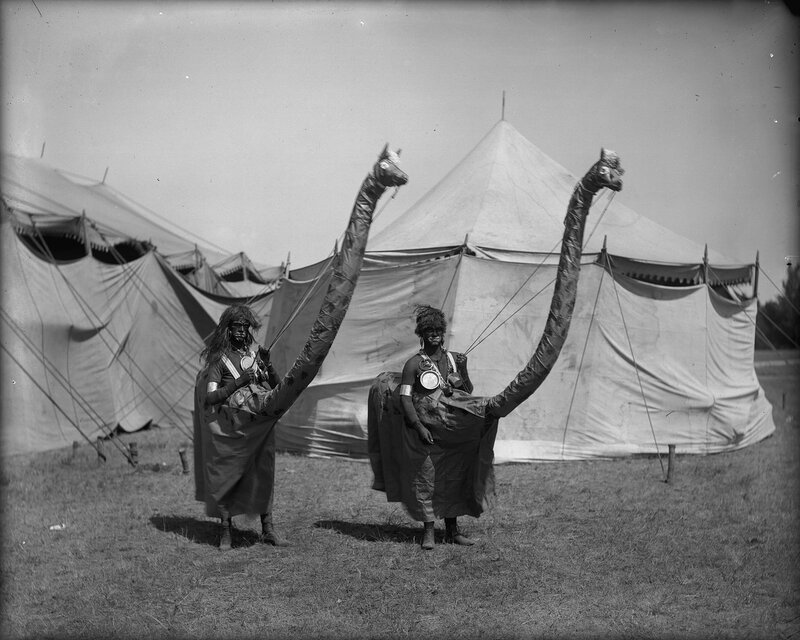 Native American men who are dressed as giraffes pose near a circus tent, Sunflower (Flower) Carnival, Colorado Springs, El Paso County, Colorado, 1898