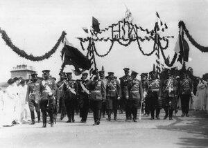 Императоры Николай II, Вильгельм II и сопровождающие офицеры проходят под триумфальной аркой, украшенной флагами и цветами в честь приезда Вильгельма II.