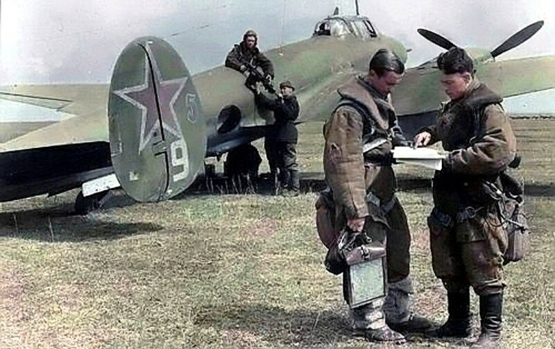 Пилот со штурманом пикирующего бомбардировщика Пе-2 обсуждают выход и заход на цель. Стрелок-радист  принимает  вооружение у механика.jpg
