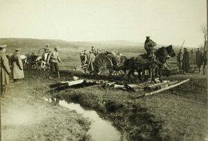 Солдаты одной из армейских частей за перевозкой полкового имущества в повозках через гать.