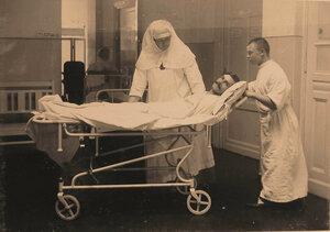 Санитар и сестра милосердия перевозят раненого в перевязочную.