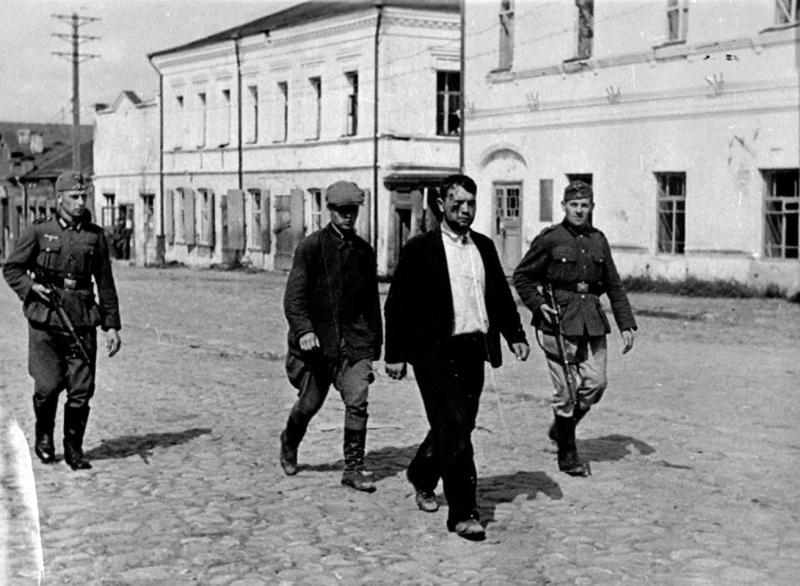 Немецкий патруль ведет пойманных переодетых советских солдат