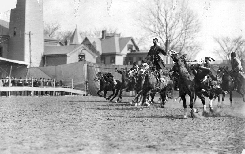 A group of Russian Georgian Cossacks on horseback ride through a dirt arena (possibly Ambrose Park or Madison Square Garden) for Buffalo Bill's Wild West Show, 1901