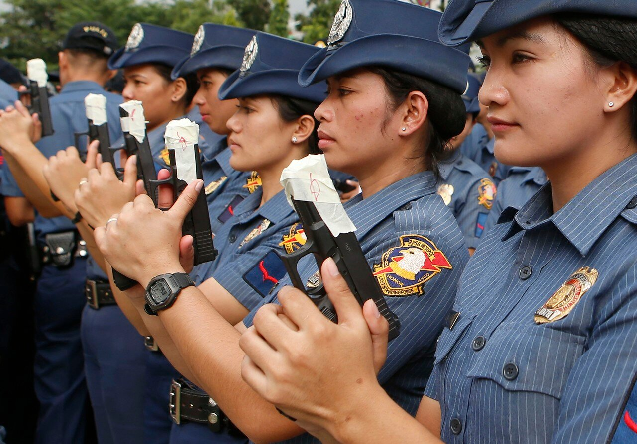 Female members of the Philippine National Police hold their service pistols that are covered with tape during the sealing of the muzzles of firearms at the National Capital Region Police Office in Taguig