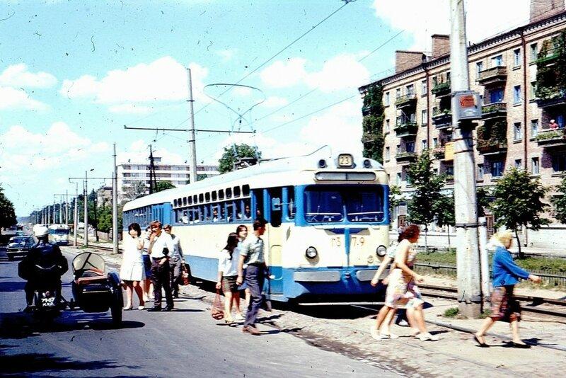 Общественный транспорт в Киеве и балконы домов в зелени.