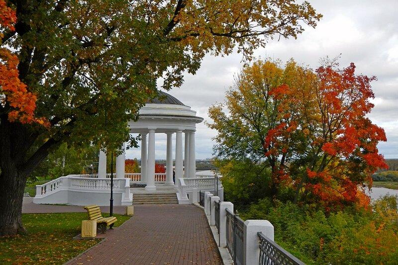 Осень на набережной в Александровском саду: прикрытая веткой дуба беседка, усыпанные листьями дорожки и красный клён