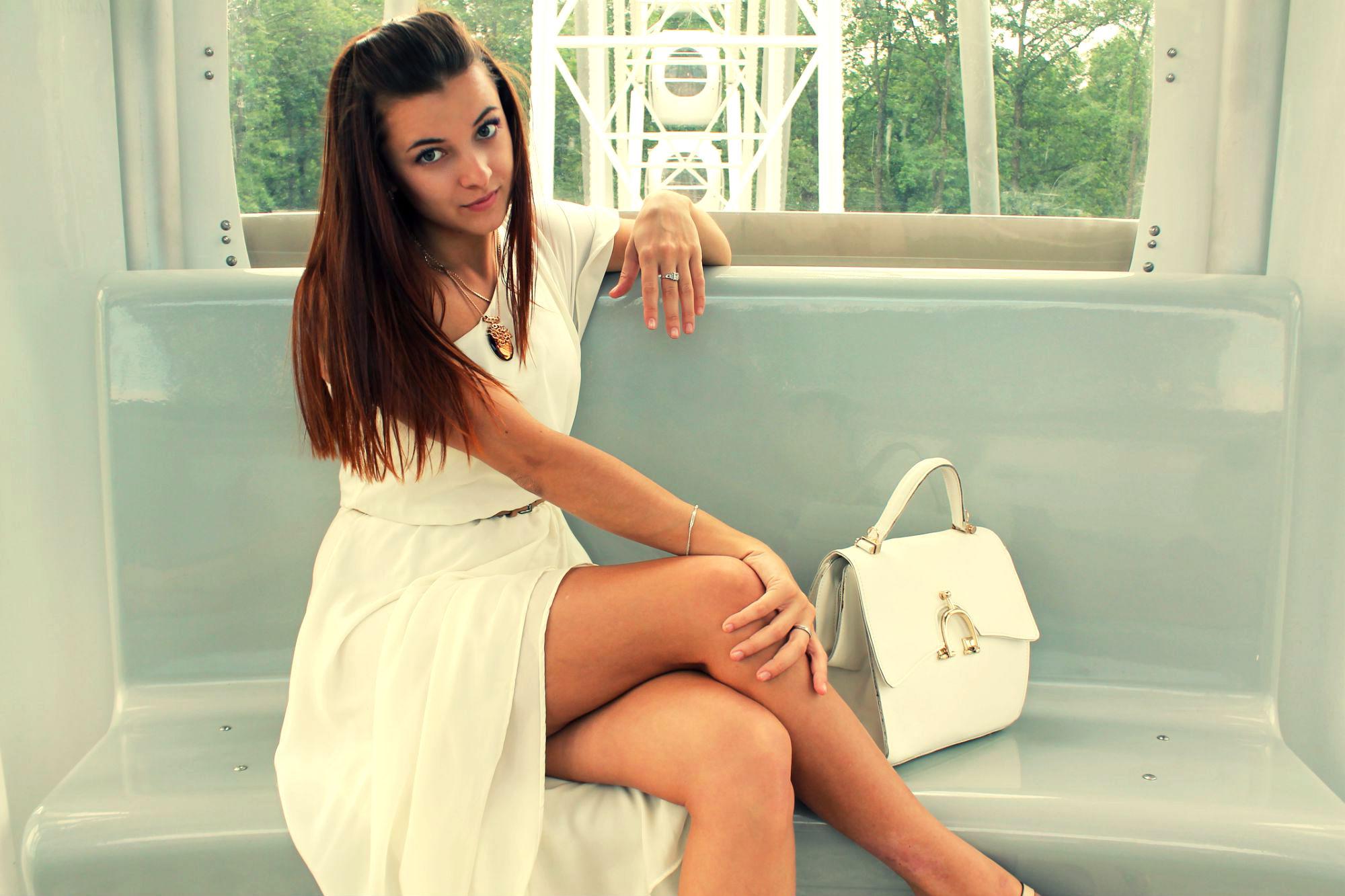 Девушка в бежевом платье на диване с сумочкой