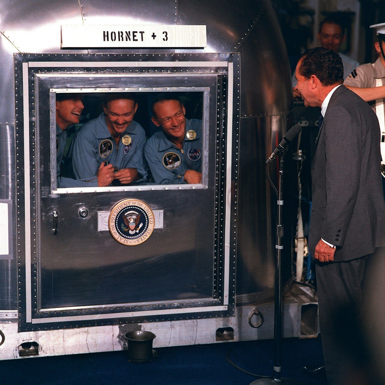 Никсон приветствовал астронавтов через стекло двери карантинного фургона. На снимке: Президент Никсон посетил астронавтов во время их пребывания в карантине
