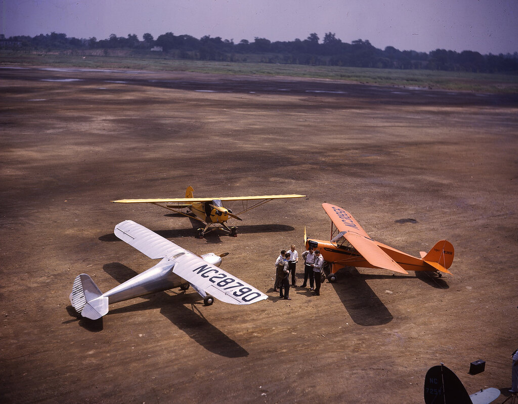 Yellow Piper J-3C-65 Cub (rn NC-25773), orange Aeronca 65-TL (rn NC-31956) and silver Luscombe Model 8 Silvaire (rn NC-28790) training planes on the ground in a circle
