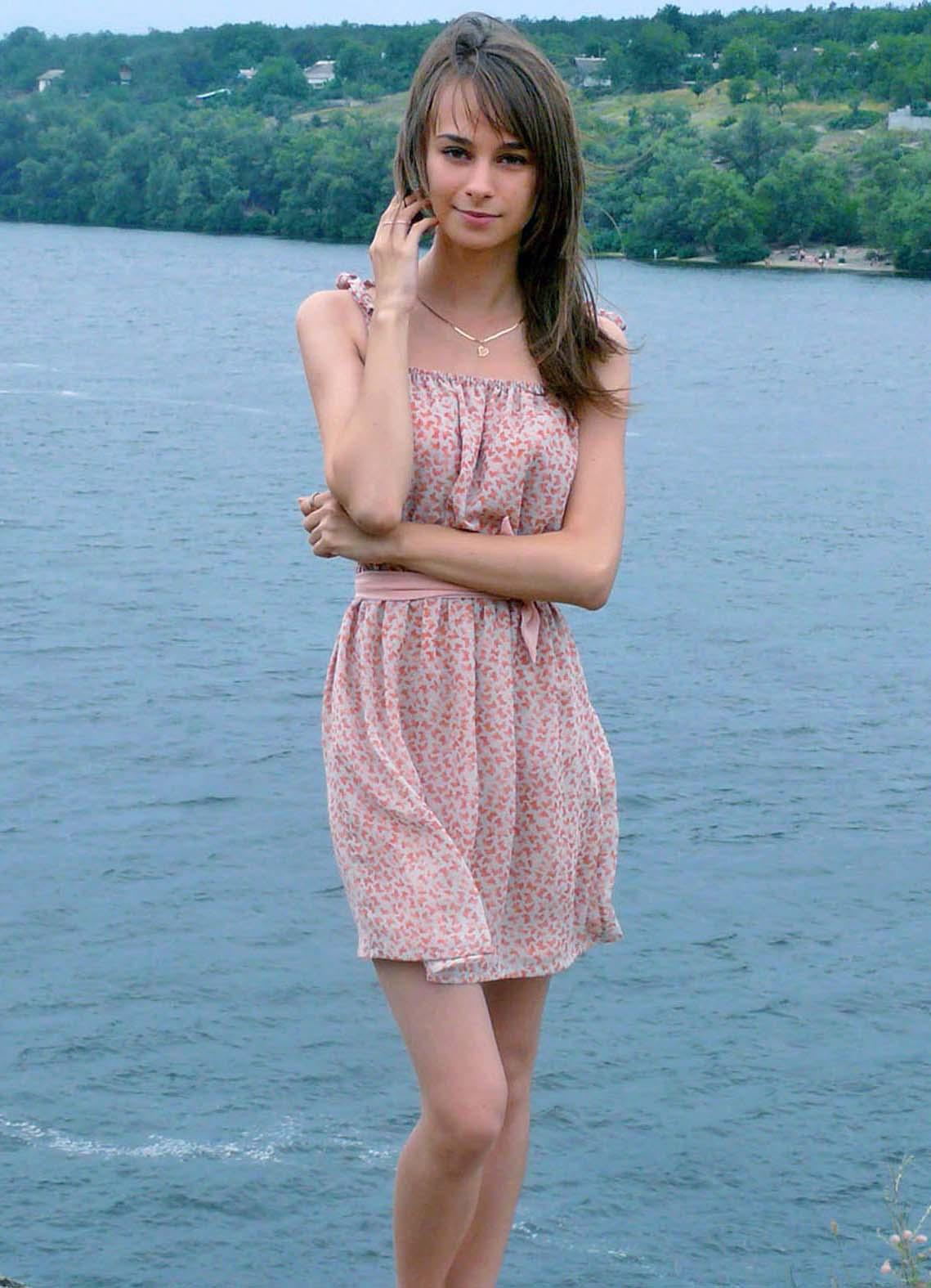 Юная девчонка в платье на фоне реки