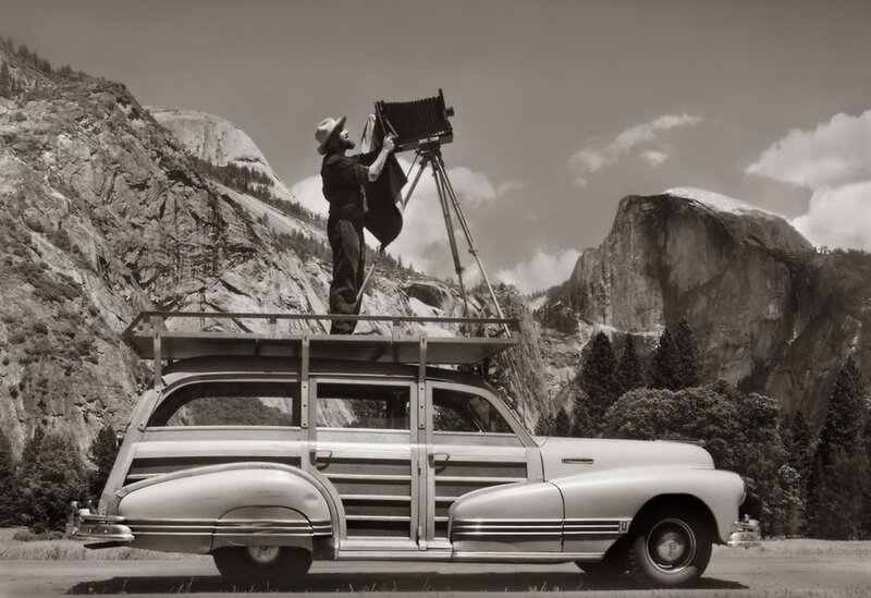 Ansel Adams prepares his camera in a National Park.jpg