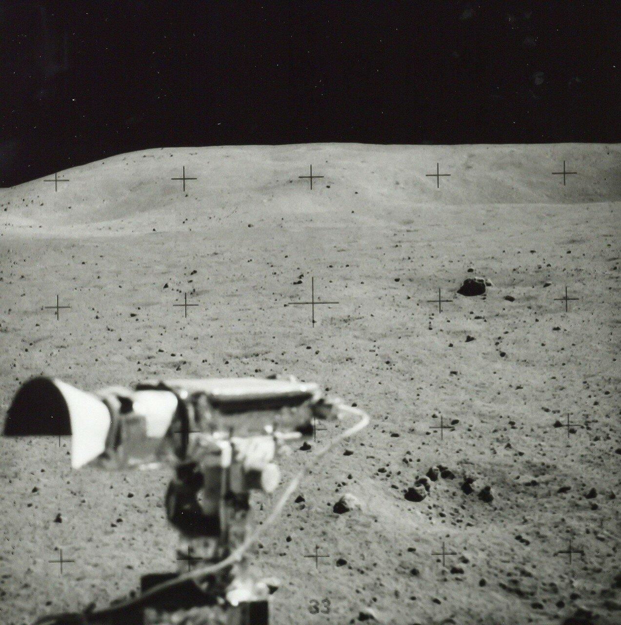 Вскоре астронавты остановились у россыпи больших валунов, некоторые из них достигали 2—3 м в поперечнике. Общий пробег «Ровера» от начала второй поездки составил 7,9 км, до лунного модуля по прямой оставалось 2,9 км.На снимке: Лунные пейзажи  из «Ровера»
