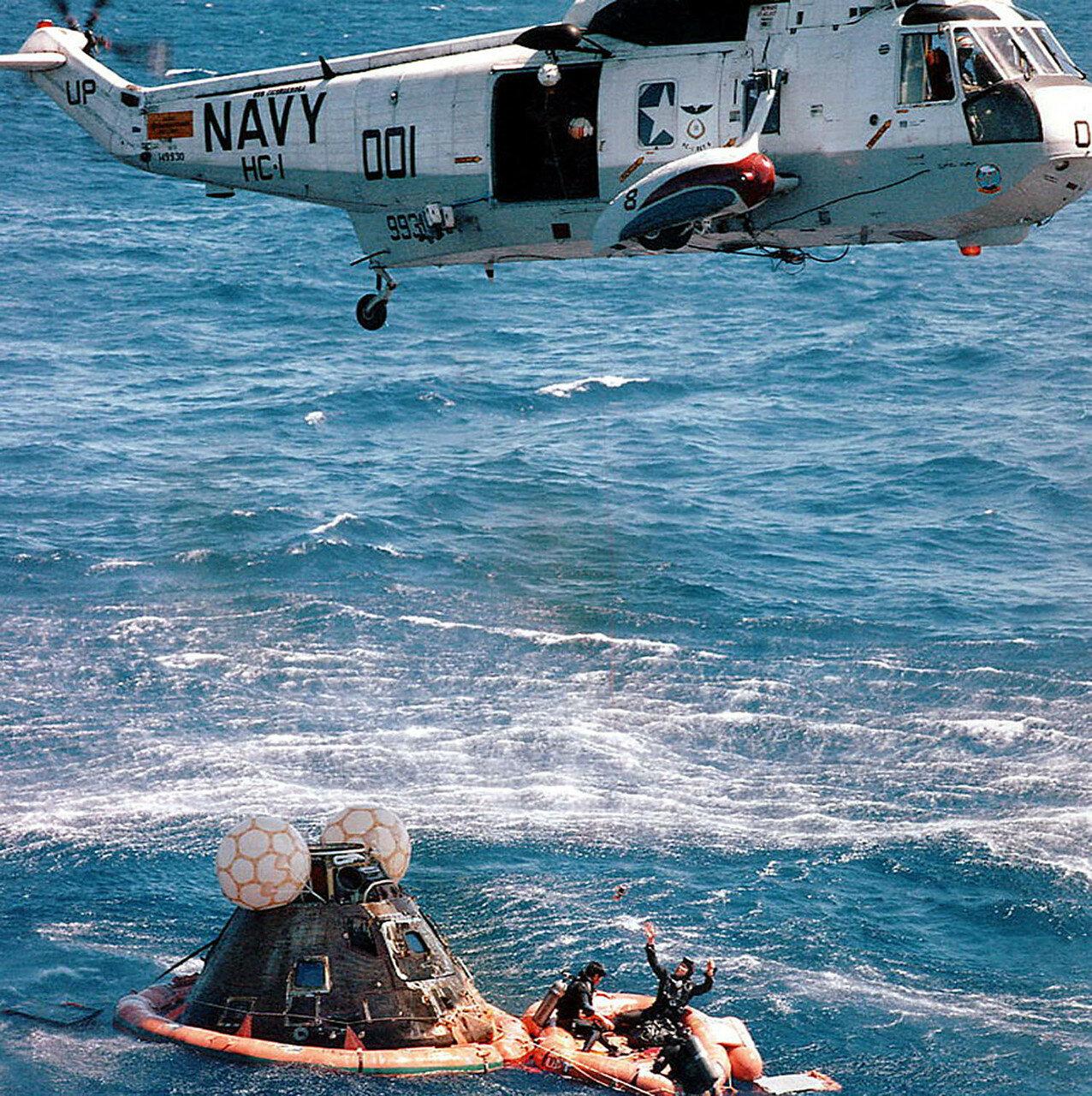 «Аполлон-16» приводнился в 5,5 км от расчётной точки и в 5 км от поискового корабля. Поисково-спасательная операция была проведена в рекордные сроки. На снимке: «Аполлон-16» вскоре после приводнения. В спасательной шлюпке — пловцы ВМФ США