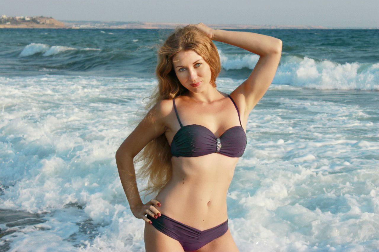 Рыжая девчонка  в купальнике на фоне волн