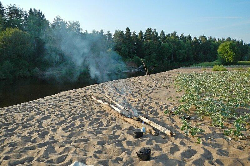 Песчаный берег реки Белой холуницы, заросли лопухов, костёр и котелки