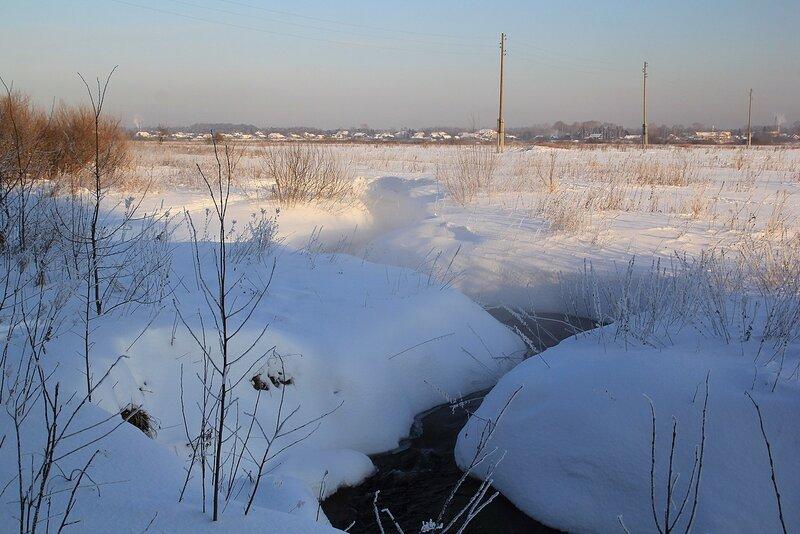 Незамерзающий ручей и пар над ним в морозный день в Заречном парке города Кирова