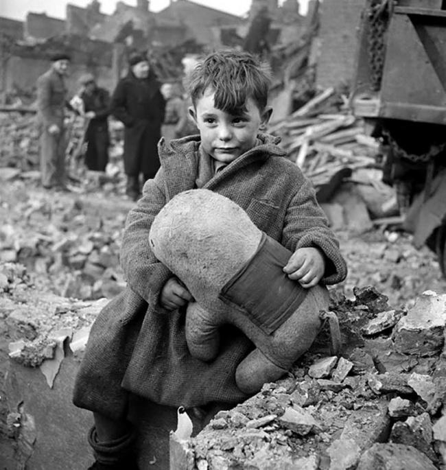 Малыш сосвоим медвежонком наразрушенной улице Лондона, 1945г.
