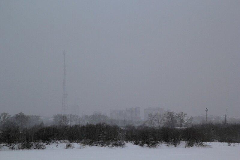 Город Киров и телевышка в снежной дымке с противоположного берега реки Вятки из Заречного парка зимой