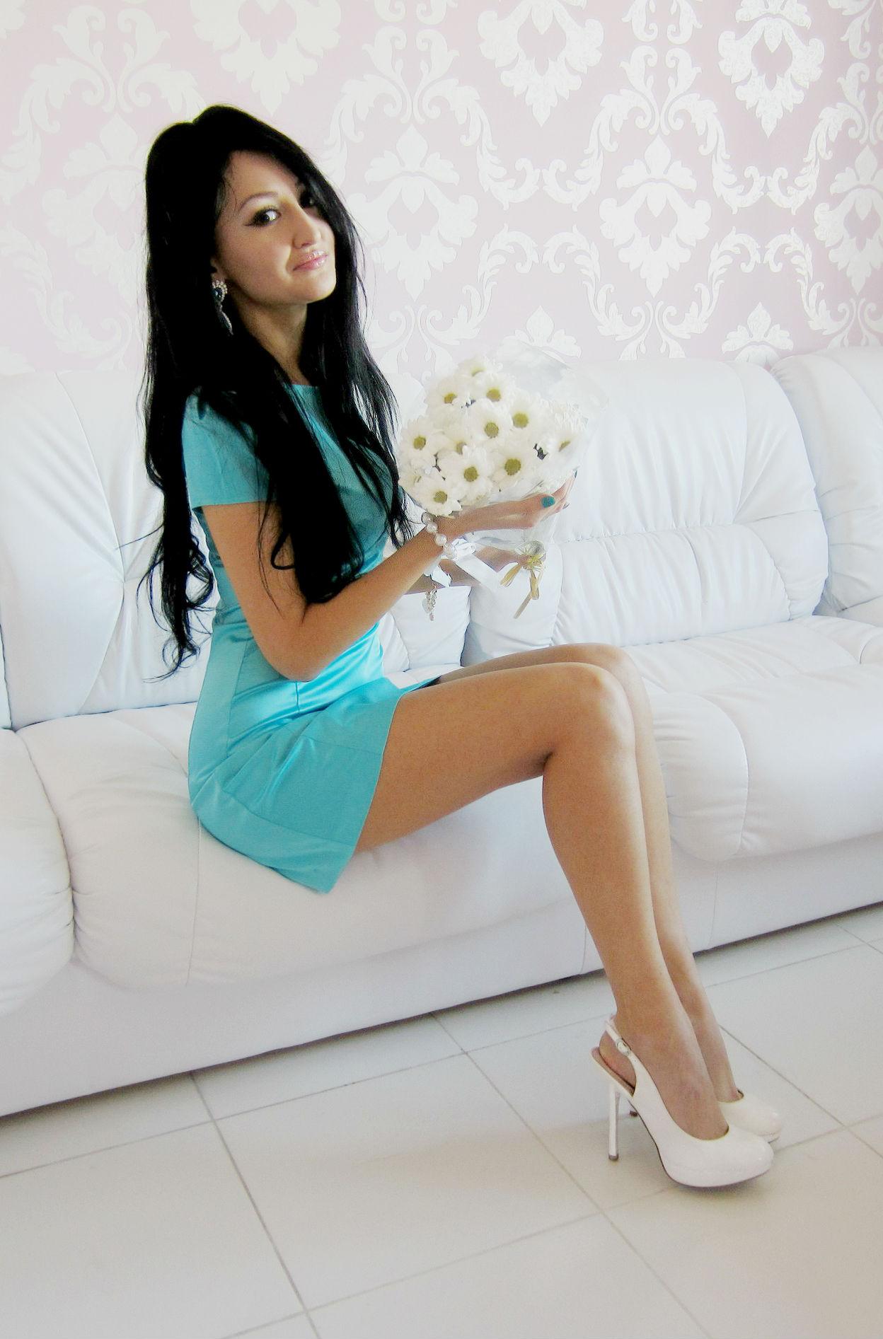 Девушка в вечернем платье с букетом ромашек