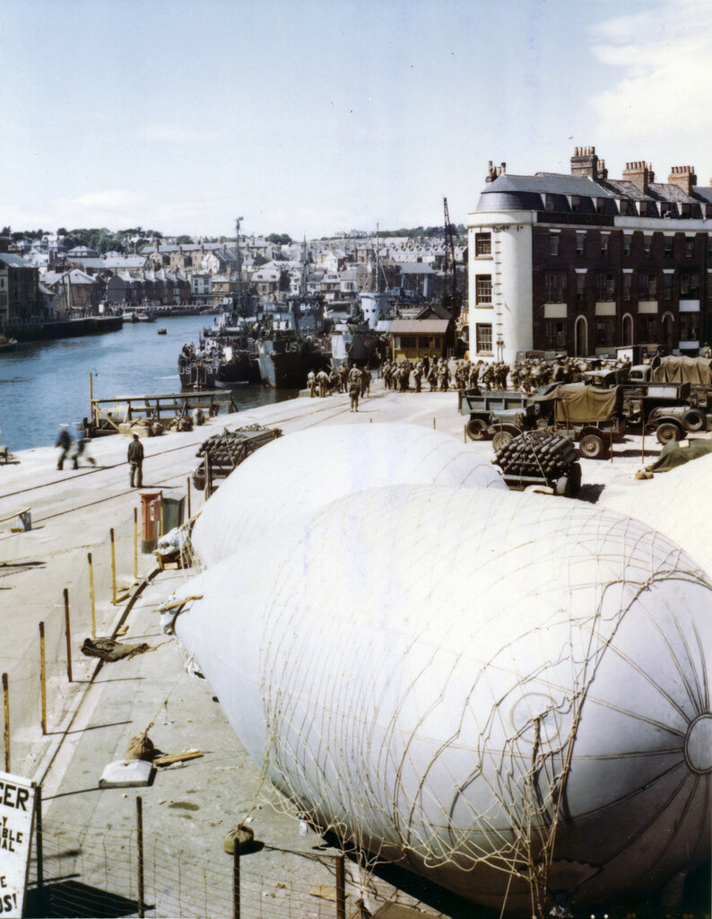 American troops load onto L.S.I.'s at a port in Britain where barrage balloons have been anchored for protection against strafing and low level bombings.
