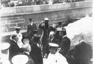 Французский президент Раймон Пуанкаре с группой встречающих на катере у причала.