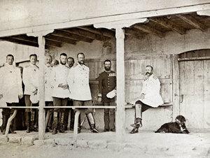Пред къщата на хаджи Николи, в която се помещава Главната щаб-квартира на руската войска - отдясно наляво: Н.В. Императорът Александър II (седнал), румънският княз Карол I, Великият княз Николай Николаевич, Великият княз Сергей Александрович и други висши офицери, крайният вляво - бъдещият български княз Александър Батенберг, Горна Студена край Свищов, август 1877 г.